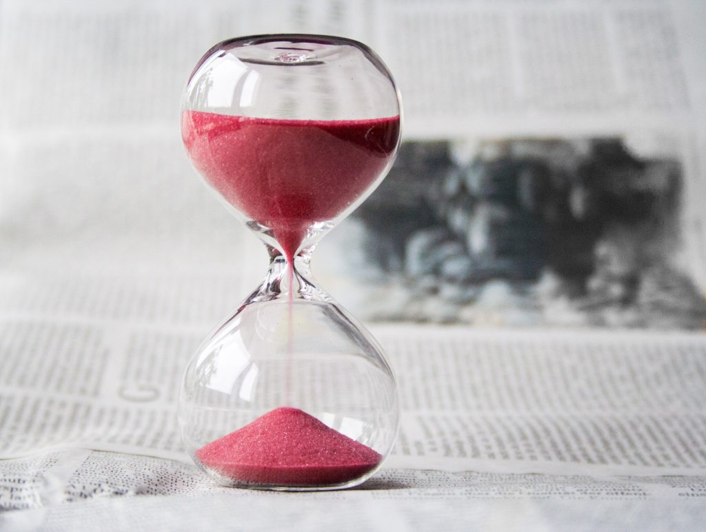 Hourglass with running red sand on an open newspaper