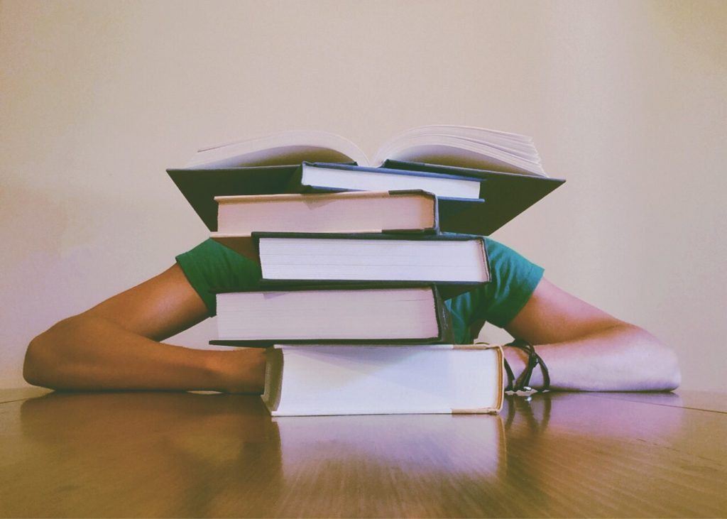 Person studying with head down behind a large pile of books.